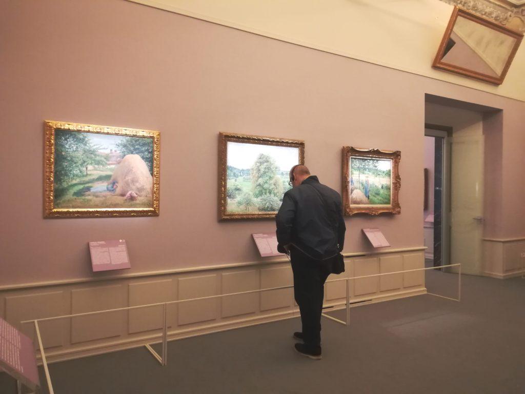 Un visitatore tra le opere di Camille Pissaro esposte a Palazzo Bonaparte